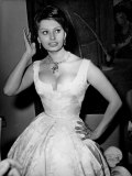 Sophia Loren.  Talk about bellissimo—the original Italian bombshell was known for wasp-waisted dresses, dangling earrings that accentuated her slim neck, and always some helpless and agog shmuck on her arm. Here is she primping in Berlin at a July 1959 ball.